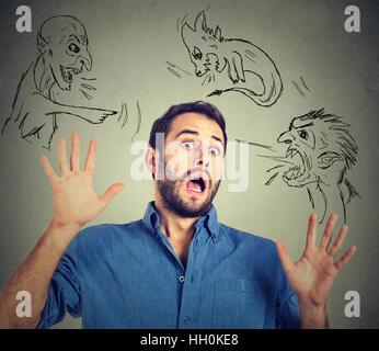 Male gli uomini malvagi puntando ha sottolineato l'uomo. Disperata paura uomo isolato su sfondo grigio. Negative Foto Stock