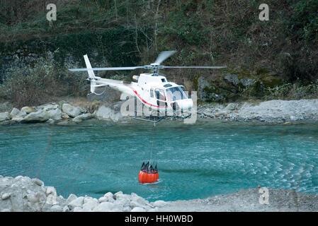 Elicottero a raccogliere acqua in un secchio da un fiume di montagna per la lotta antincendio e radioestesia fiamme, Foto Stock