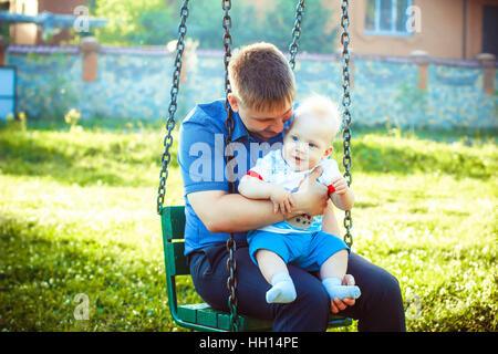 Padre abbracciando il Bambino sulle ginocchia Foto Stock