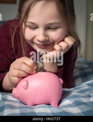 Ragazza giovane salvare la sua Euro denaro in un salvadanaio. Foto Stock