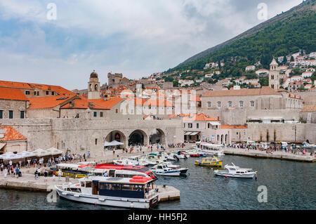 Storico, Dubrovnik Croazia porto con barche da pesca, traghetti, storico di tegole rosse con tetti di edifici e Foto Stock
