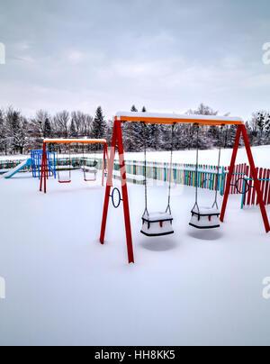 Parco giochi per bambini coperte di neve in inverno Foto Stock