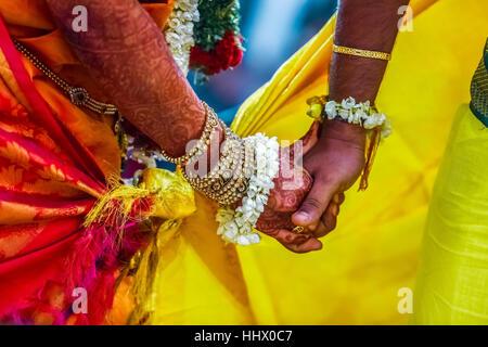 Lo sposo detiene spose in mano nel sud indiana tradizionale cerimonia di nozze Foto Stock