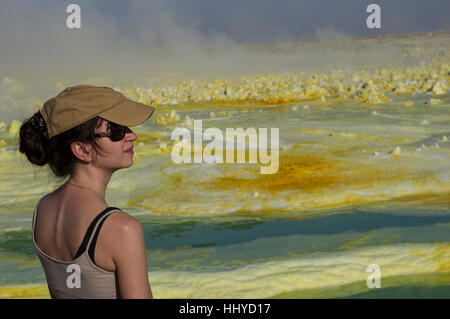 La donna nel cappello e occhiali da sole a Dalol, Danakil depressione, Etiopia e i vividi colori di giallo e verde Foto Stock
