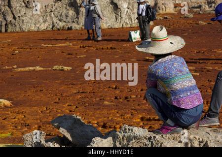 Donna con cappello di paglia e colorate shirt accovacciata accanto al color ruggine formazioni di cristallo a Dallol, Foto Stock
