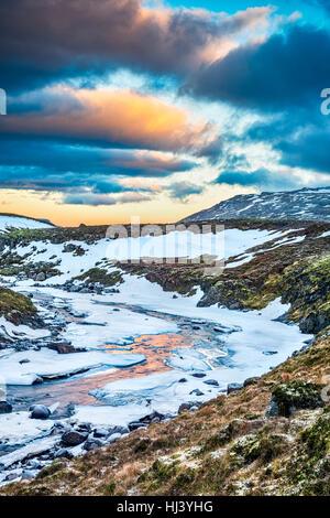 Un fiume congelato nelle Highlands di Islanda incorniciata dai cieli pastello e scoscesi offre paesaggio panoramico Foto Stock