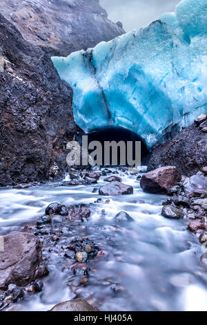 Una caverna di ghiaccio in Islanda formata al di sotto di un ghiacciaio è la fusione e la formazione di un fiume muggiti attraverso la bocca della grotta.