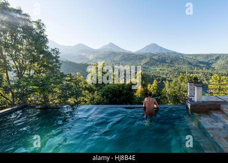 Uomo che guarda oltre il paesaggio, piscina, Munduk, Bali, Indonesia Foto Stock