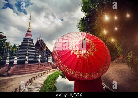 Donna con turistico rosso tailandese tradizionale ombrellone in nero tempio Wat Phan Tao in Chiang Mai Thailandia Foto Stock