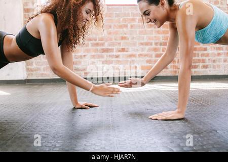 Vista laterale colpo di due giovani donne che esercitano insieme in palestra. Le donne facendo pushups insieme. Foto Stock