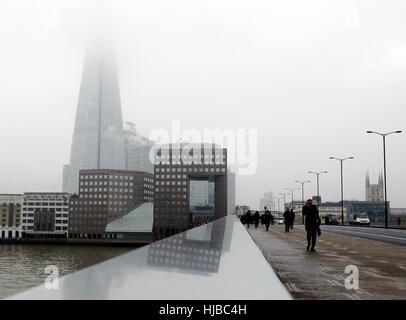 Pedoni cross London Bridge con il Coccio avvolta nella nebbia dietro di loro, come nebbia fitta causato interruzioni Foto Stock