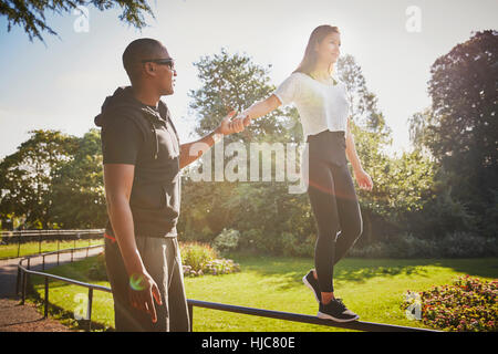Donna che mantiene le mani con personal trainer camminando sul recinto del parco Foto Stock