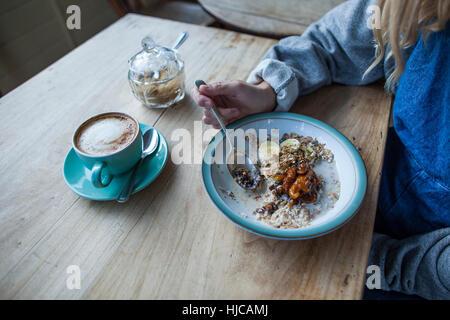 Giovane donna in cafe, mangiare muesli, metà sezione Foto Stock