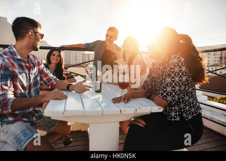 Un gruppo di giovani seduti attorno a un tavolo con bevande. Giovani uomini e donne aventi parti sul tetto in serata.