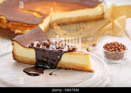 Cheesecake fetta con il cioccolato fuso e le sfere di cioccolato Foto Stock