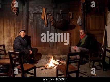 Un vecchio uomo e un turista occidentale sedersi intorno al fuoco nel salotto di una casa colonica in un remoto Foto Stock