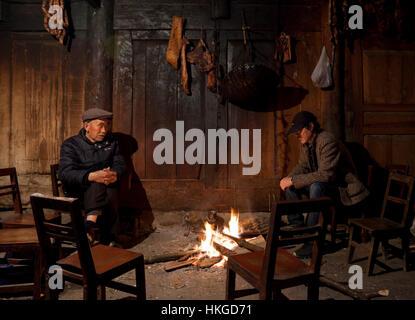 Un vecchio uomo e suo nipote di sedersi intorno al fuoco nel salotto di una casa colonica in un remoto villaggio Foto Stock