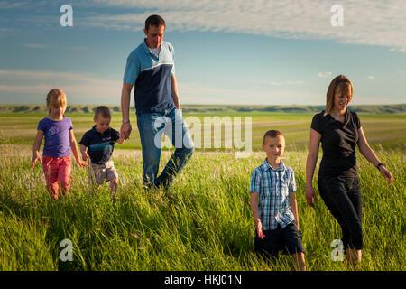 Una famiglia passeggiate attraverso un campo di fattoria; Herschel, Saskatchewan, Canada Foto Stock