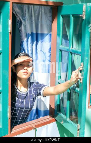 Donna che guarda attraverso la finestra e si copre la faccia da sun. Una giovane donna guarda fuori dalla finestra Foto Stock