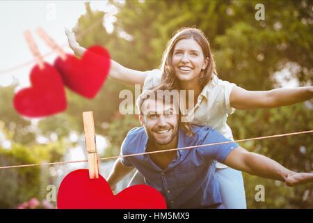 L uomo dando un piggyback ride per donna Foto Stock
