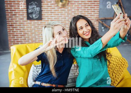 Due bella giovane donna facendo selfie in un cafe, migliori amici ragazze insieme divertendosi, creando uno stile Foto Stock