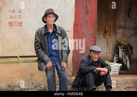 Due vecchi cinesi uomo davanti alla loro casa e fumare una tubazione, nella provincia dello Yunnan in Cina Foto Stock