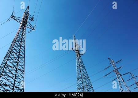 Grande ad alta tensione torri elettrico sotto il cielo blu Foto Stock