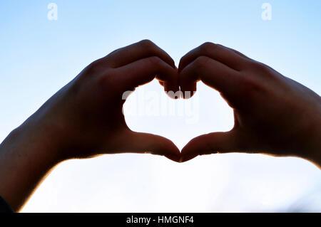 Due mani creando una forma di cuore contro il cielo blu Foto Stock