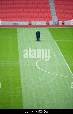 Lone groundsman taglia l'erba su un ampio campo di calcio. Foto Stock