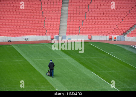 Lone uomo taglia il turf presso un grande vuoto allo stadio di calcio. Foto Stock
