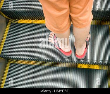 Parte inferiore delle gambe e dei piedi di uomo in flip flop su escalator, Putrajaya, Malaysia Foto Stock
