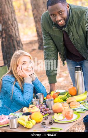 Sorridente amici divertendosi in campeggio Foto Stock