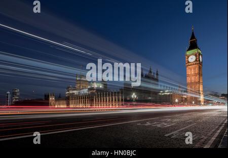 Il movimento sfocati semaforo sentieri sul Westminster Bridge e le case del parlamento di Londra, Inghilterra, Regno Foto Stock
