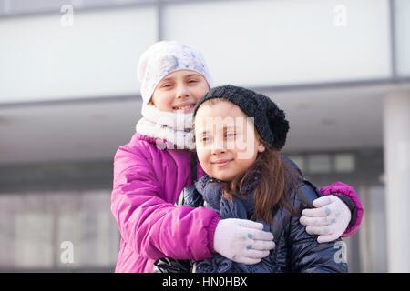Due bambine con cappelli e sciarpe giocare Foto Stock