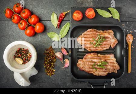 Bistecca con spezie e i pomodori cotti in padella per grigliare su un tavolo scuro vista superiore Foto Stock