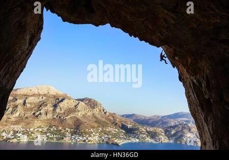 Giovane uomo arrampicate lungo le rocce Foto Stock
