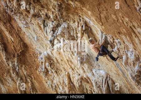 Stanco di scalatore in appoggio prima di raggiungere il prossimo appiglio. Percorso impegnativo sulla rupe a strapiombo. Foto Stock