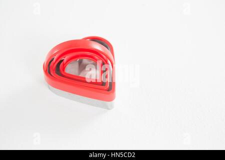 Forma di cuore cookie cutter in diverse dimensioni su sfondo bianco Foto Stock