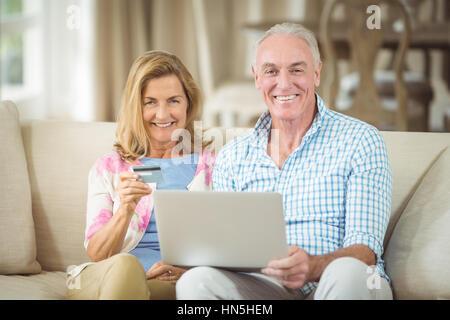 Ritratto di sorridente coppia senior facendo shopping online su laptop nel salotto di casa Foto Stock