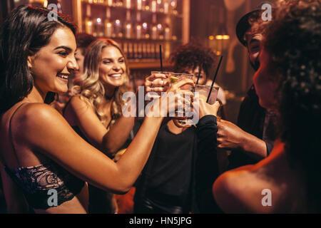 Un gruppo di giovani con i cocktail al night club. Migliori amici partying in un pub e tostatura di bevande. Foto Stock