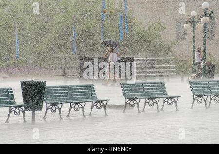 La città di Quebec, Canada - 27 Luglio 2014: Giovane a piedi sotto la pioggia con ombrello sul Boardwalk street Foto Stock