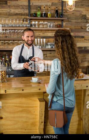 La donna il pagamento fattura tramite lo smartphone utilizzando la tecnologia NFC in cafe Foto Stock