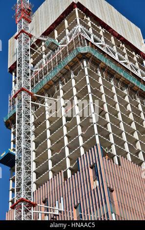 In prossimità di un edificio torre in costruzione che mostra il nucleo ed il mantello. Foto Stock