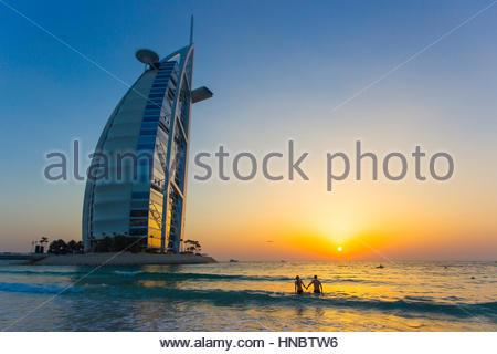 Un giovane per mano e guardare il tramonto nel Golfo Persico, vicino al Burj Al Arab hotel. Foto Stock