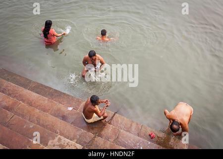 Un uomo e donna orante e la balneazione, nel ghats del fiume Gange, Varanasi, Uttar Pradesh, India. Foto Stock
