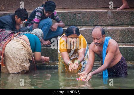 Uomo e donna che fa l'offerta, nel ghats del fiume Gange, Varanasi, Uttar Pradesh, India. Foto Stock