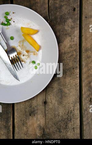 Vista aerea di avanzi su una piastra con coltello e forchetta su un rustico sfondo di legno Foto Stock