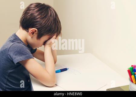 Stanco bambino facendo i compiti a casa. Il ragazzo stufi e si copre il viso con le mani. Istruzione, scuola, difficoltà Foto Stock