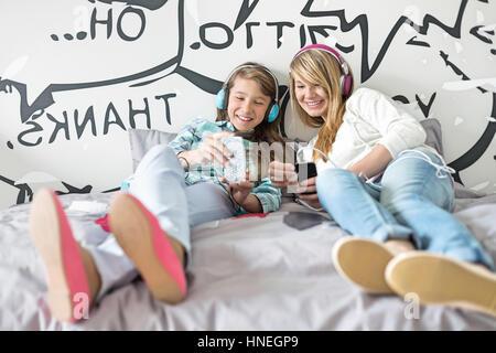 Sorelle rilassati ascoltando la musica a casa Foto Stock
