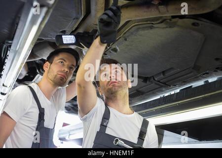 Meccanica maschio esaminando auto in officina Foto Stock